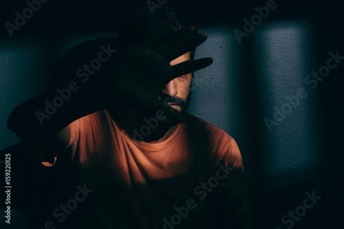 Fotografía  Prisoner man in dark cell hiding face with shame