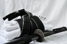 Black Belt Martial Arts On White Background. Japanese (Chinese) Traditional Katana Sword. Hieroglyph Translation Means Union.