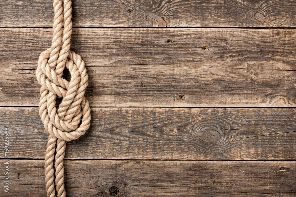 Fototapeta Rope knot on wooden board