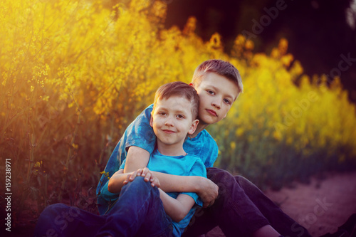 Valokuva  Two cute sibling boys hugging and having fun near the canola field