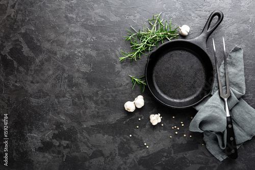 Fotografía  Empty cast iron frying pan on dark grey culinary background, view from above