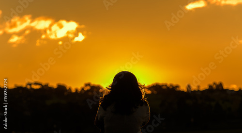 Fototapeta  One female with long hair is sitting alone looking into the sun in silhouette