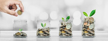Hand Putting Coin In Glass Bottles With Plants Glowing, Saving Money And Investment  Concepts