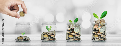 Fototapeta Hand putting coin in glass bottles with plants glowing, Saving money and investment  concepts obraz
