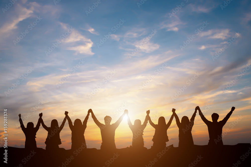 Fototapeta Silhouette of happy business team making high hands in sunset sky background for business teamwork concept
