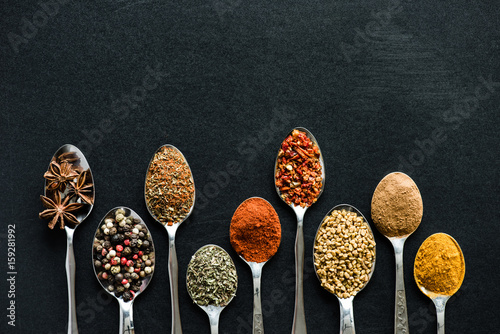 top view of various spices and herbs in metal spoons isolated on black