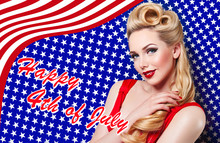 Holiday US Independence Day, The Fourth Of July. Beautiful Young Girl In Retro Style Smiling On The Background Of The American Flag. The Blonde Pinup. Postcard, Advertising. Hair Curls, Red Lips.