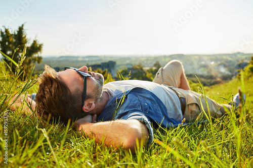 Spoed Foto op Canvas Ontspanning Man lying on grass enjoying peaceful sunny day