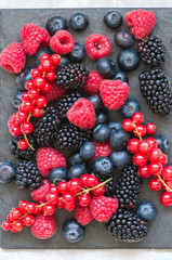 Mix of berries raspberries red currants blueberries and blackberries on black slate board. White stone background.  Top view.