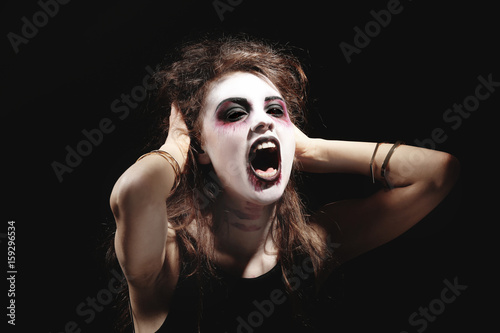 Young woman in color contact lenses, with Halloween makeup on black background Wallpaper Mural