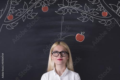 Business woman and falling apple on the blackboard Fototapet
