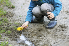 A Child Plays In The Dirt.