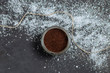 brown scrub into a glass jar with jute thread loose shiny artificial snow on a dark grey black background copyspace close-up