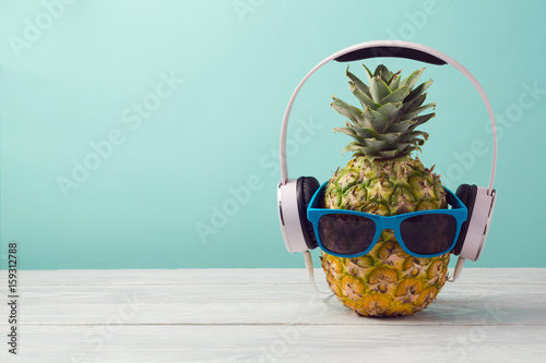 Magasin de musique Pineapple with headphones and sunglasses on wooden table over mint background. Tropical summer vacation and beach party concept.