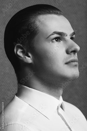 Male beauty concept. Profile portrait of young man with perfect haircut wearing white classic shirt. Old Hollywood star style. Wet hair. Close up.