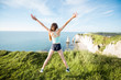 Young playful woman in sportswear jumping outdors on the beautiful rocky coastline background near Etretat town in France
