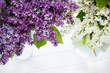A bouquet of lilacs in front of light background, natural colors, top view