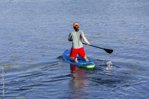 Plakat Człowiek na pokładzie wiosła wiosłując na jezioro