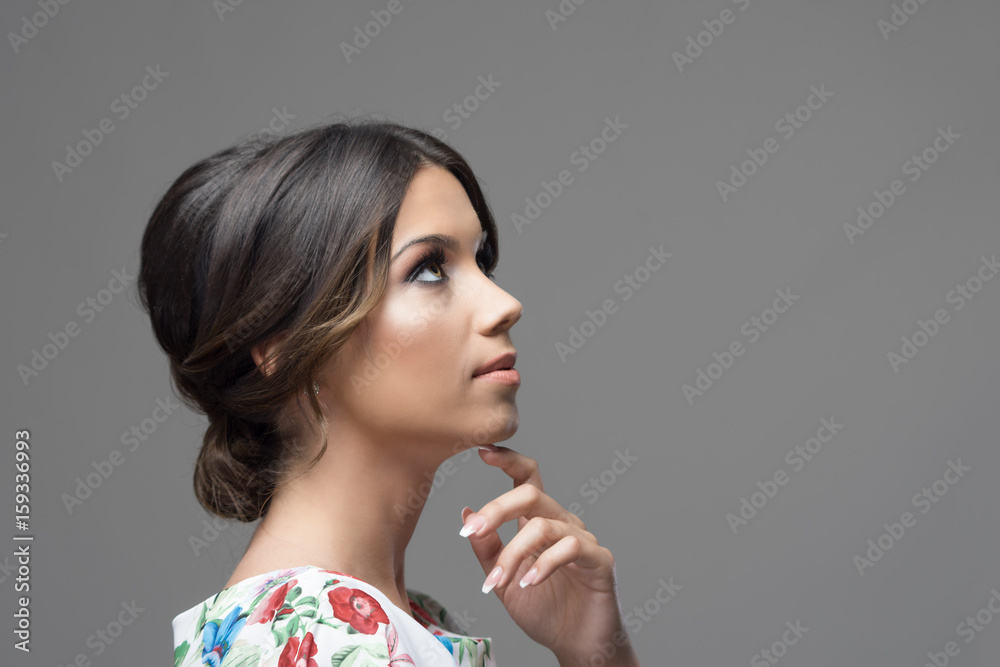Fototapeta Gorgeous profile of latin hispanic beauty woman with finger under chin thinking and looking up at copyspace over gray studio background.