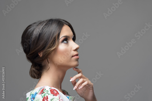 Fototapeta Gorgeous profile of latin hispanic beauty woman with finger under chin thinking and looking up at copyspace over gray studio background. obraz
