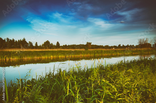 Cadres-photo bureau Inde Rural summer sunset landscape with river and dramatic colorful sky