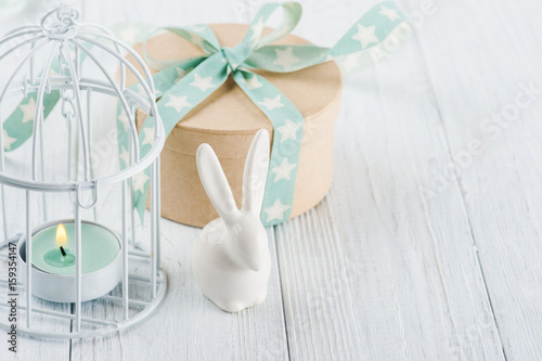 Mint green lit candle in white lantern with gift Poster