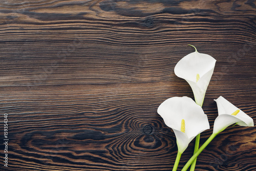 Fotografie, Obraz  White calla flowers on wooden background, top view