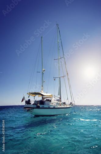 jacht-plywajacy-po-niebieskich-wodach-w-pelnym-sloncu