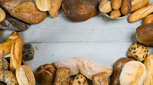 Assortment of baked bread on wooden rustic table background