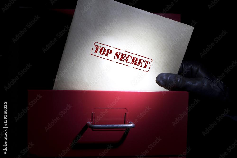 Fototapeta Looking for top secret documents in a dark.