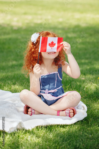 Poster Canada Portrait of cute little red-haired Caucasian girl child holding Canadian flag with red maple leaf, sitting on grass in park outside, celebrating Canada Day anniversary