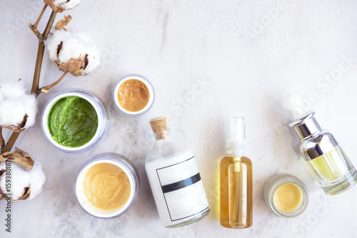 Natural skincare cosmetic products on white marble table from above. Creams, balms, masks, oils, serums. Beauty blogger concept