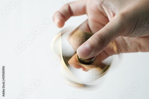 Fototapeta  Goldren metal fidget spinner spinning on table