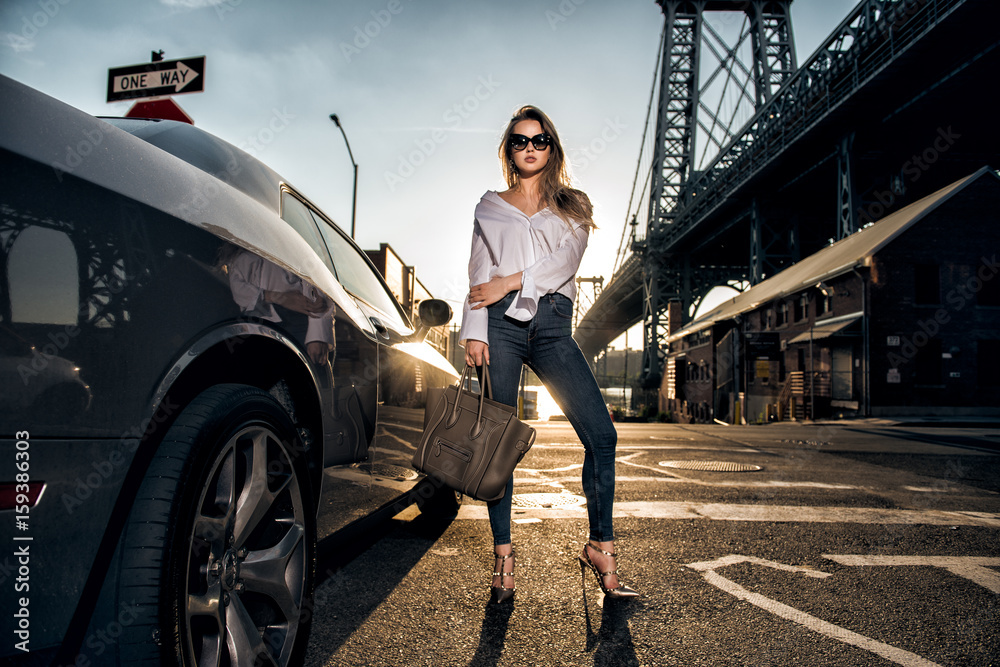 Fototapeta Beautiful fashion model woman posing with a car wearing casual street style outfit