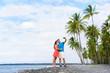 Selfie couple on Hawaii beach vacation with palm trees and volcanic black sand in Big island of Hawaii, USA. Hawaiian holidays getaway. Happy people on summer holidays.