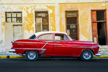 Vibrant Red Shiny Car And Ruined House In Cuba