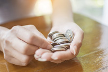 Close Up Hand Of The Woman Hold Coins And Pile Coin For Saving. Money Saving Concept