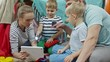 Tracking shot of mom and dad sitting on the floor and playing with kids: woman holding digital tablet and boy using flashlight