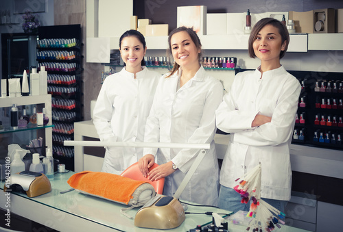 Portrait of professional manicurists at working place inviting to salon Wallpaper Mural
