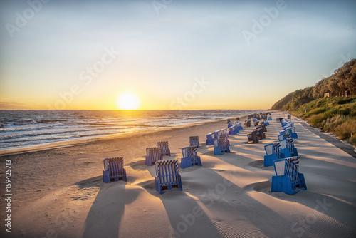 Obraz Schatten von Strankörben beim Sonnenaufgang am Strand - fototapety do salonu
