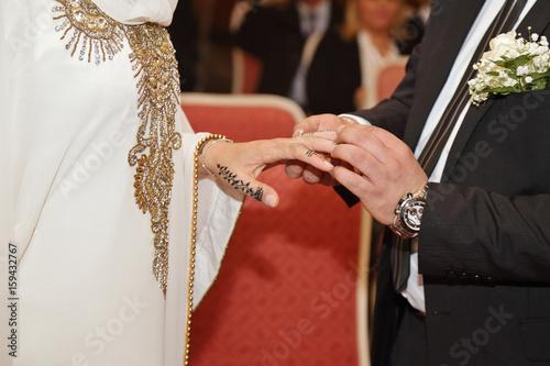Photo  couple mariage oriental avec mains dessinée au henné passant la bague au doigt