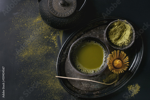 Green tea matcha powder and hot drink in black bowls standing with iron teapot, bamboo traditional tools spoon and whisk in vintage tray over dark metal background Canvas Print