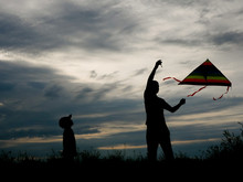 Father And Son Flying A Kite O...