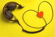 canvas print picture - headphones and heart. the concept musical. yellow beautiful background