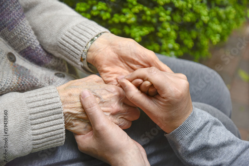 Touches the hands of an old woman - Concept of Elderly care Canvas Print