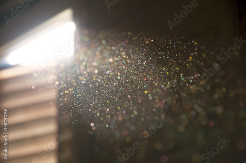 Photographie A ray of sun coming through the wooden shutters, illuminates dust on the inside of a dark room
