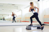 Fitness instructor making step aerobics in gym