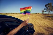 Man Waving A Small Rainbow Flag