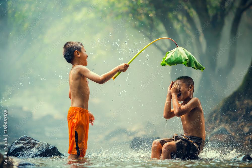 Fototapeta Childrens playing and splashing in the river
