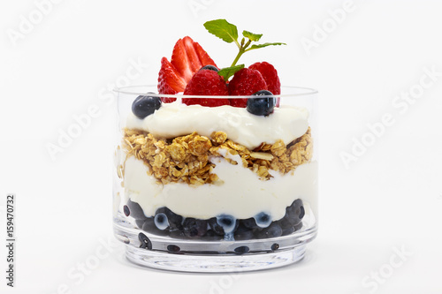 Glass jar of Greek yogurt isolated on white background from side view.